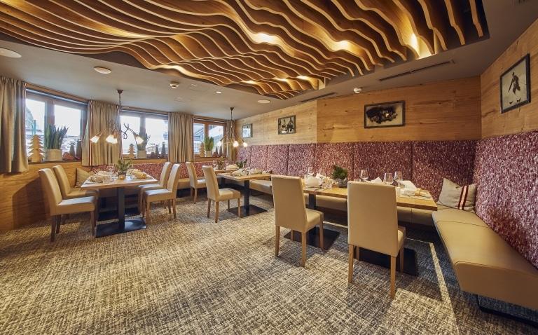 Speisesaal mit einem Design-Holzelement und vier gedeckten Tischen.