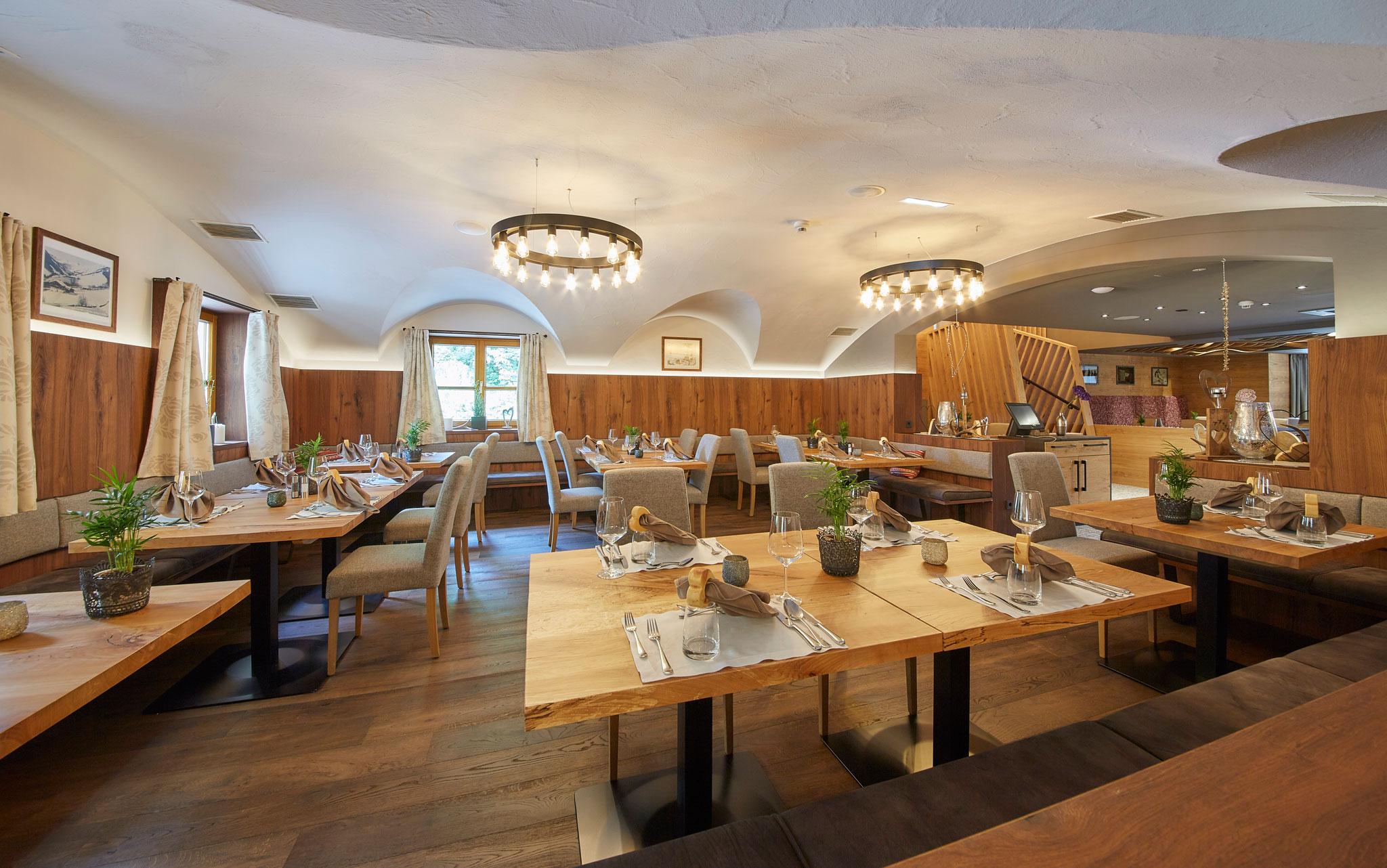 Speisesaal mit großen runden Deckenleuchten und einigen gedeckten Tischen mit Dekoration