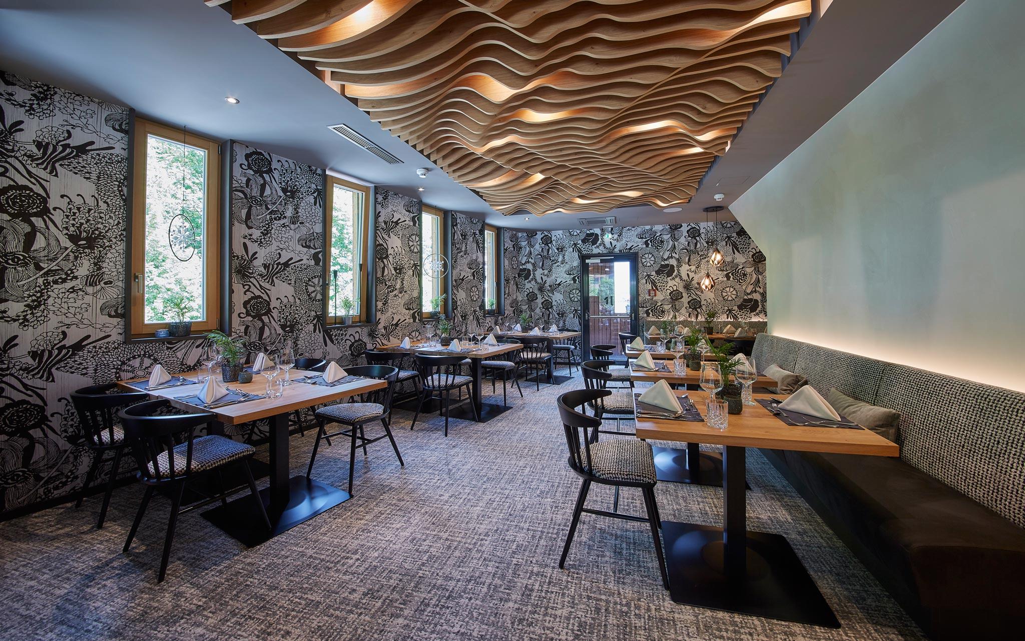 Der Speisesaal mit einem Holzelement auf der Decke sowie weiß-schwarzen Tapeten und einigen gedeckten Tischen.