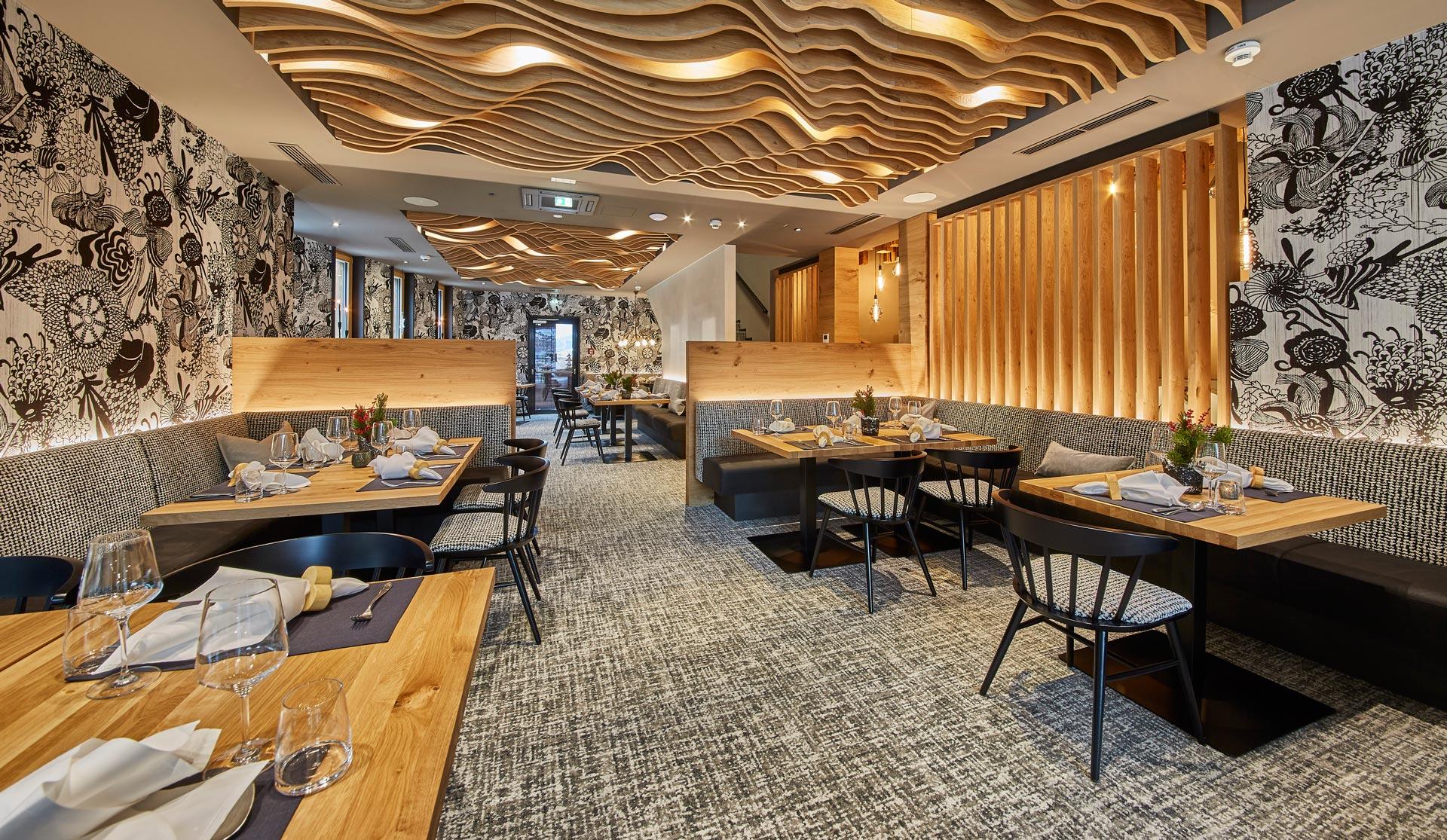Speisesaal mit dekorativer Deckenverkleidung aus Holz und schwarz-weiß gemusterten Wandtapeten