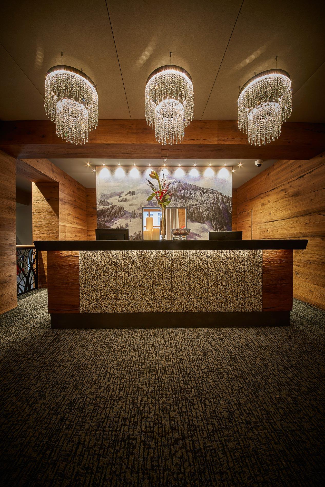 Ansicht der Rezeption mit 3 großen Deckenleuchten sowie schwarz-weiß gemustertem Teppichboden