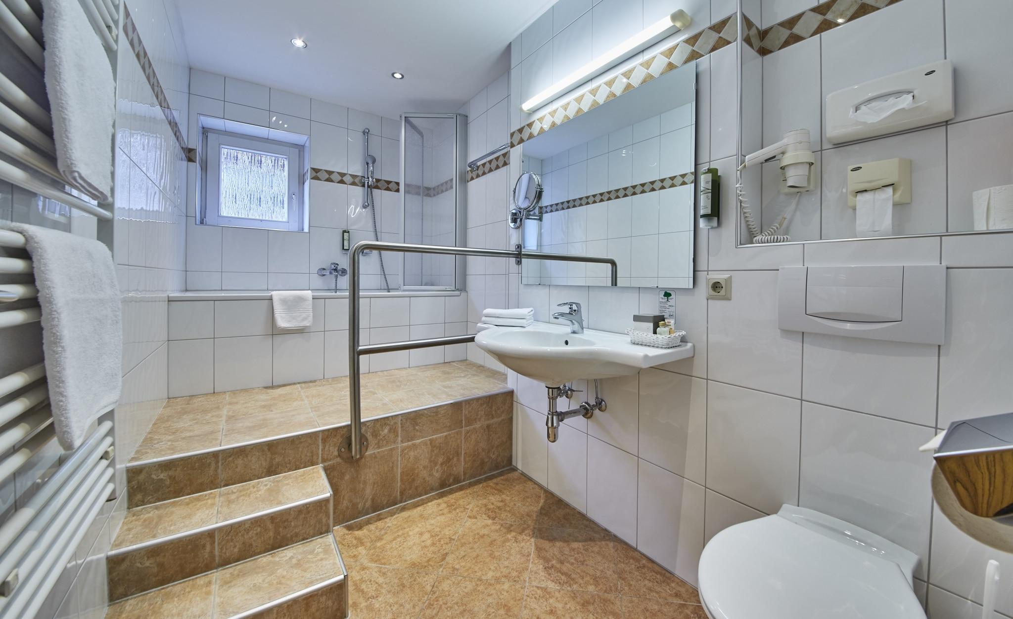 Blick in eines unserer Badezimmer mit einer Badewanne und dem Waschbecken
