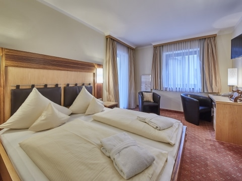 Ein Doppelbett aus Holz mit Bettdecken und Pölstern sowie einem Schreibtisch und einem TV