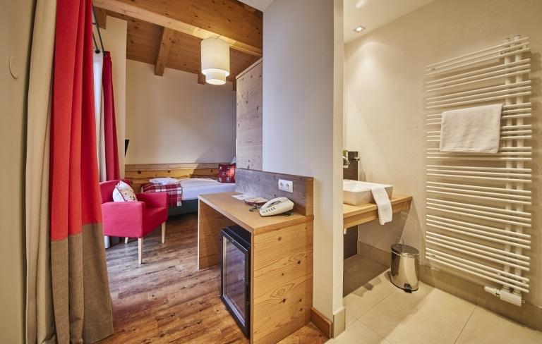 Blick in ein Einzelzimmer mit einem Bett sowie einer Minibar und dem Badezimmer