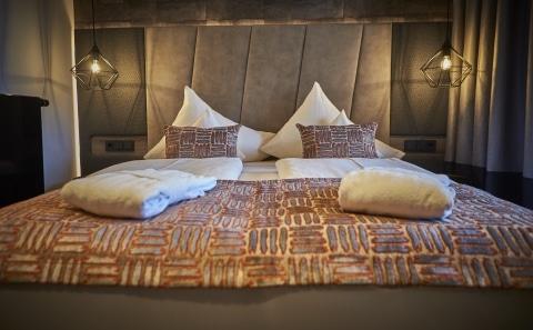 Doppelbett mit Polstern, Tagesdecke und Bademänteln