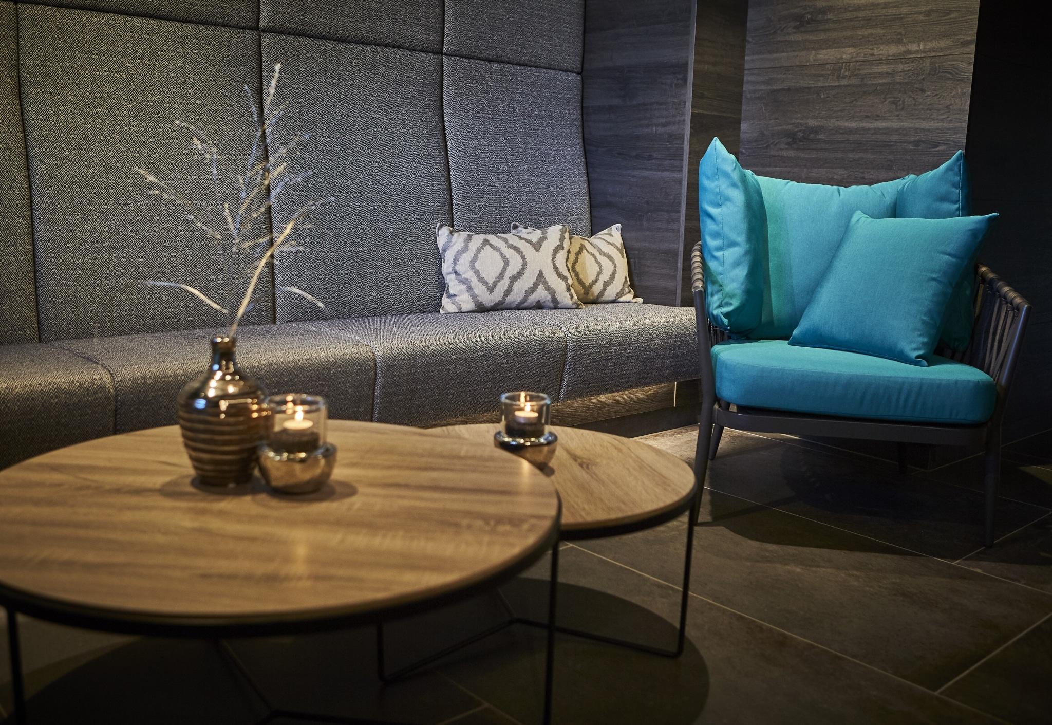 Tische, ein Stuhl und eine Sitzbank im Spa-Bereich