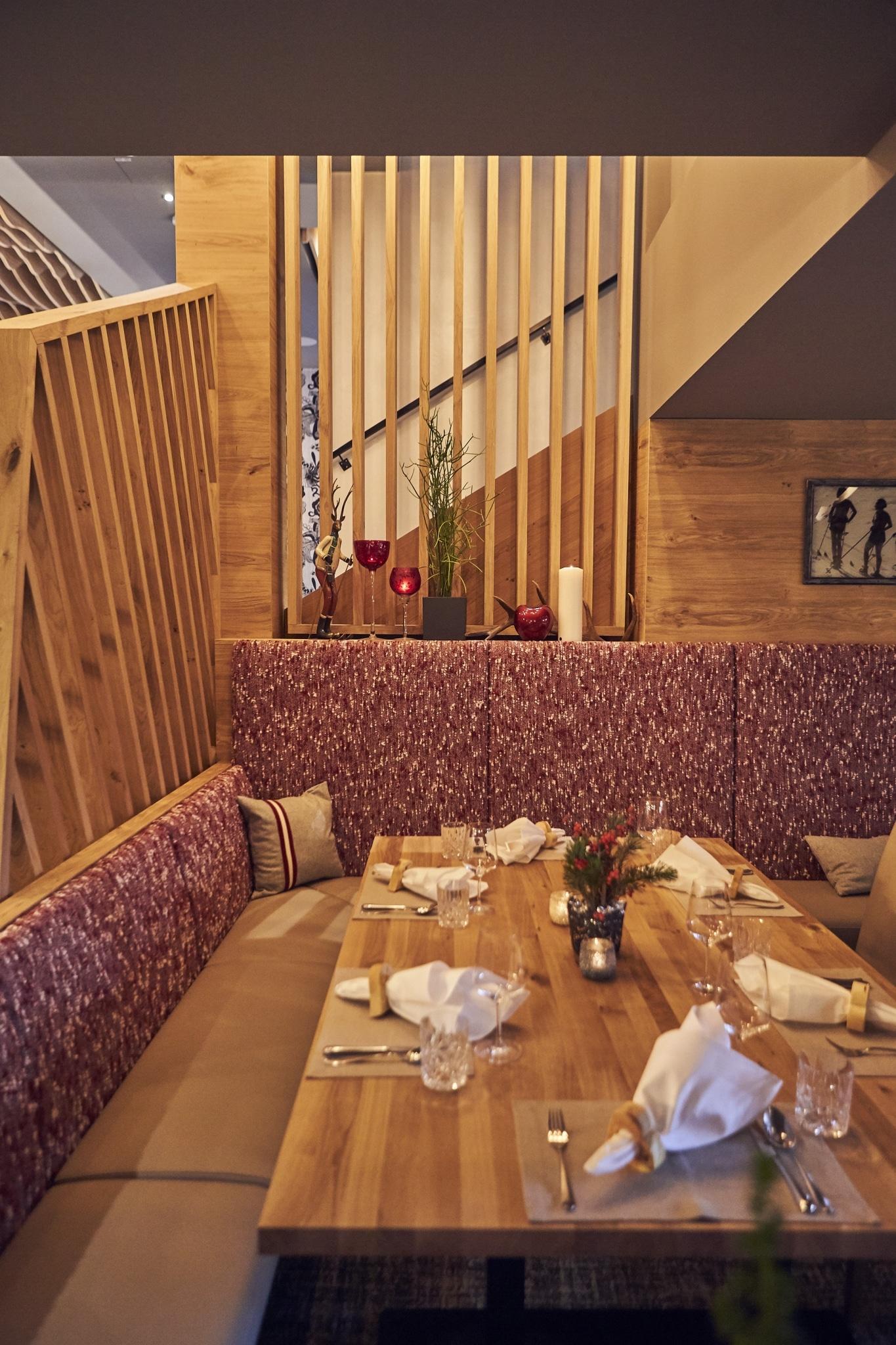 Eine Eckbank im Speisesaal mit rotem Stoff und einem gedecktem Tisch davor