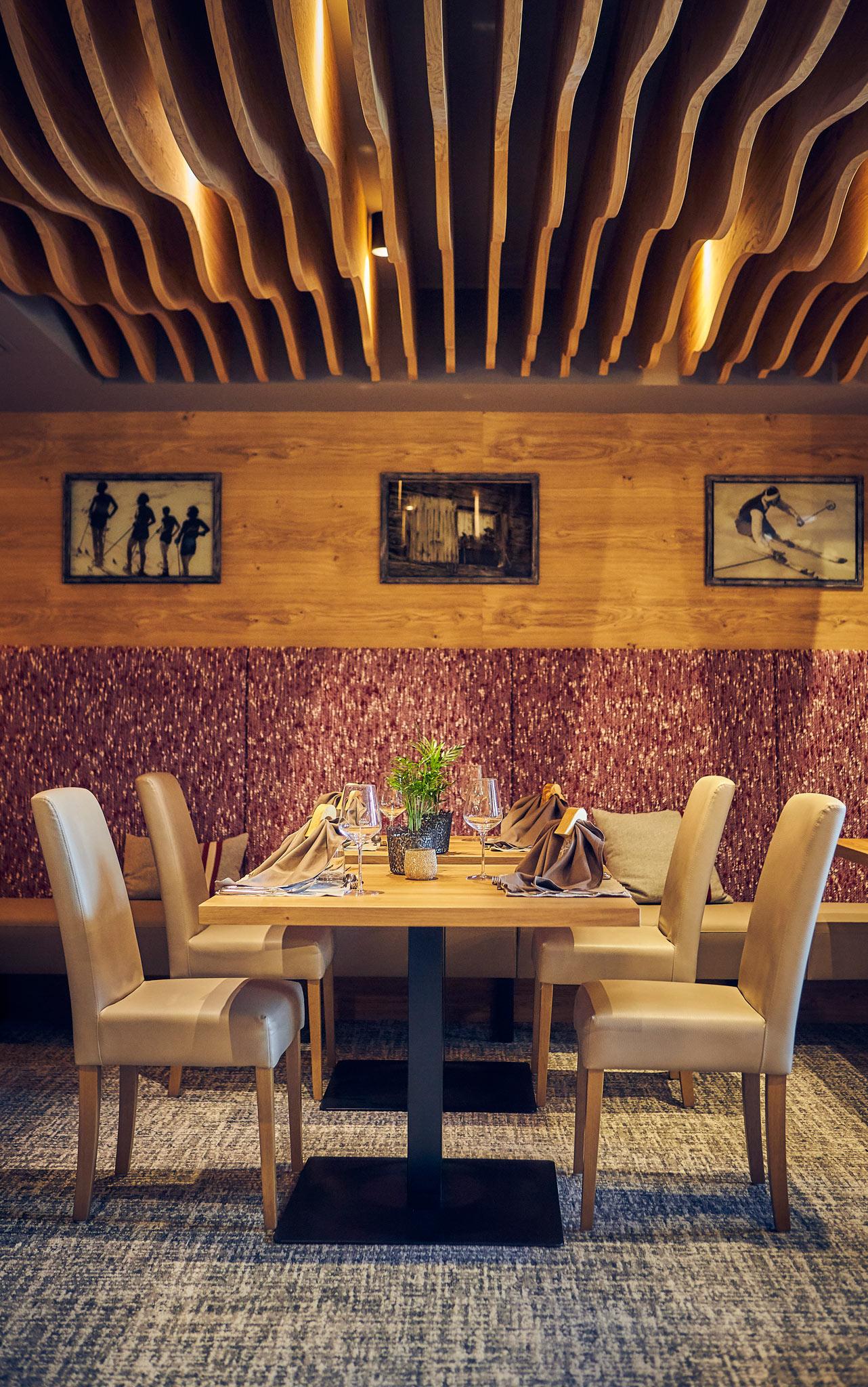 Ein gedekter Tisch im Speisesaal mit roter Polsterung der Eckbank und Lederpolsterung auf den vier Stühlen.