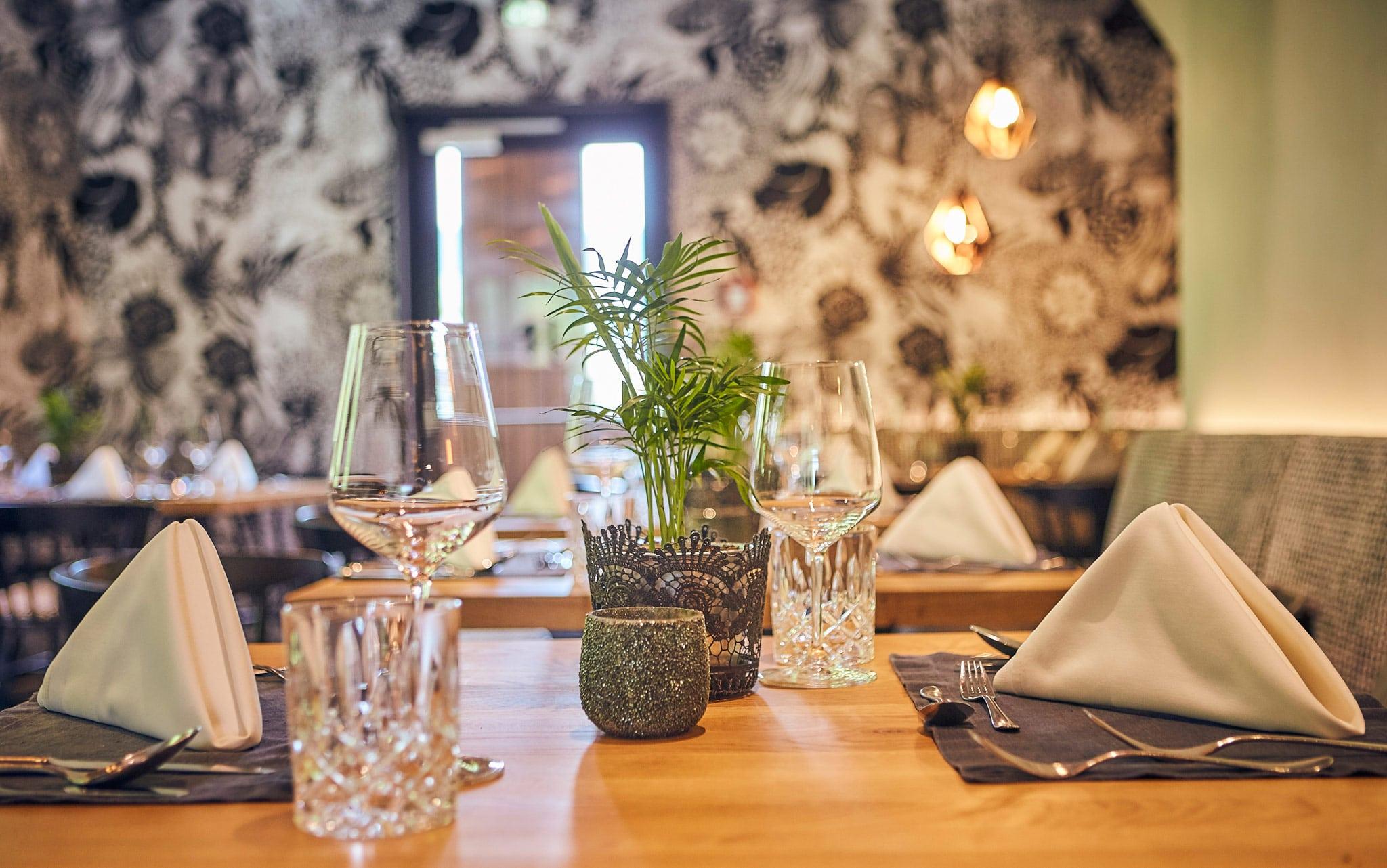 Ein gedeckter Tisch mit Besteck, Gläsern und einer grünen Pflanze als Dekoration