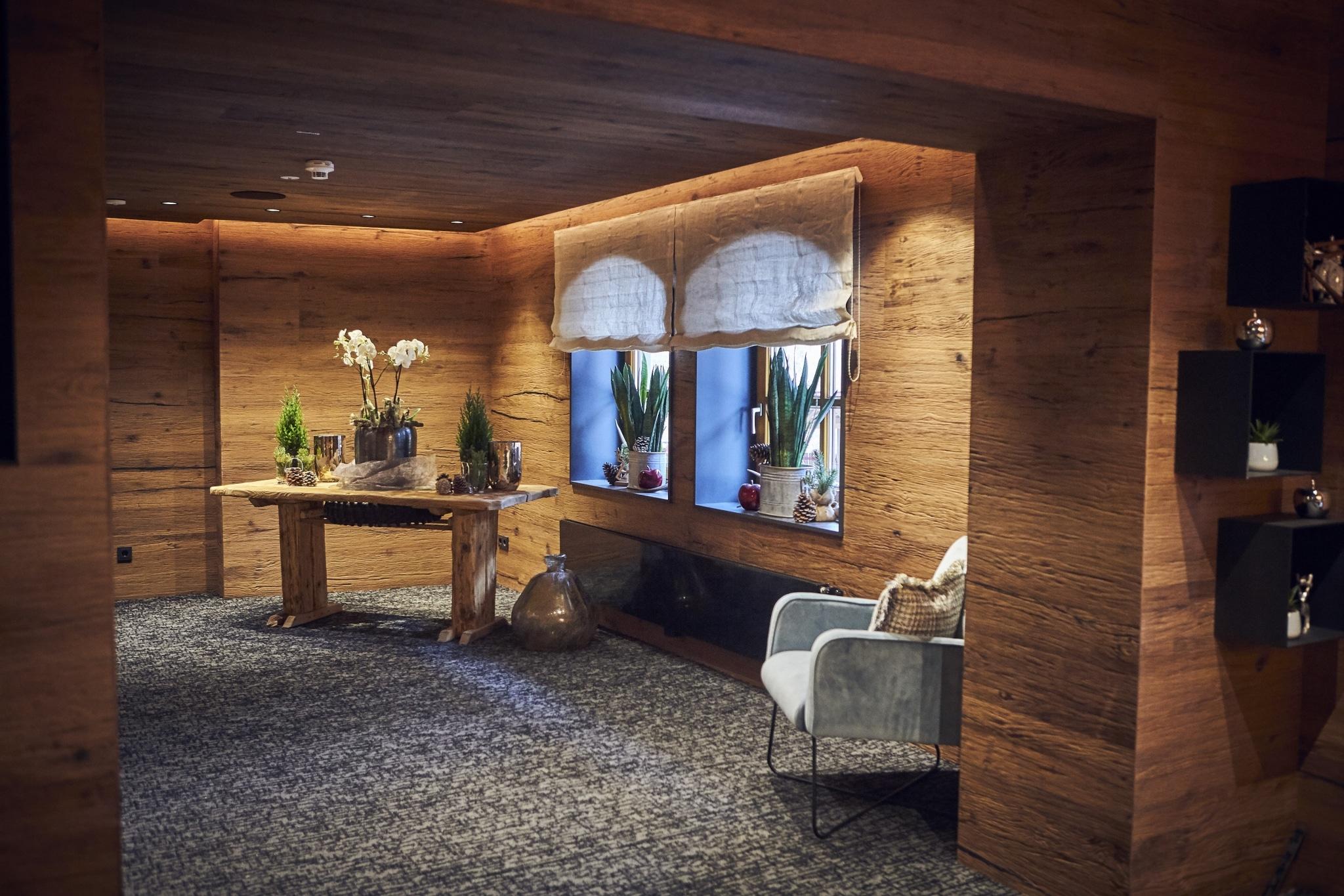 Der Eingangs- und Aufenthaltsbereich mit grauem Teppichboden und einem Holztisch mit Dekoartiekln