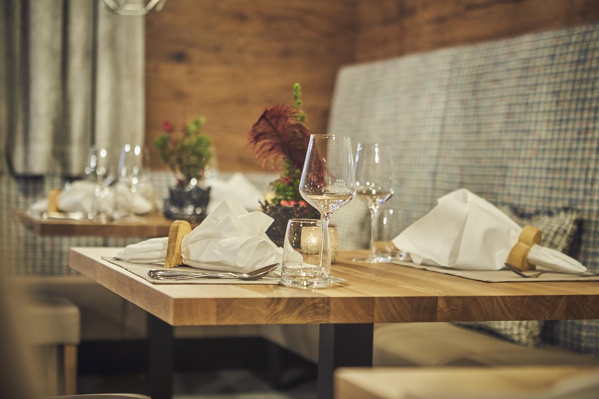 Ein gedeckter Tisch mit Gläsern, Besteck, einer Serviette und Dekoration