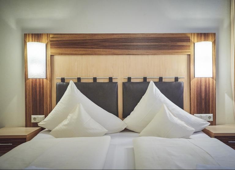 Blick auf ein Bett mit weißen Bettdecken und Pölstern