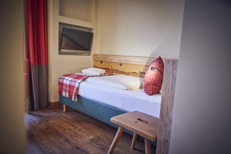 Ein Einzelbett mit weißer Bettdecke und rotem Polster sowie einem TV über dem Bettende