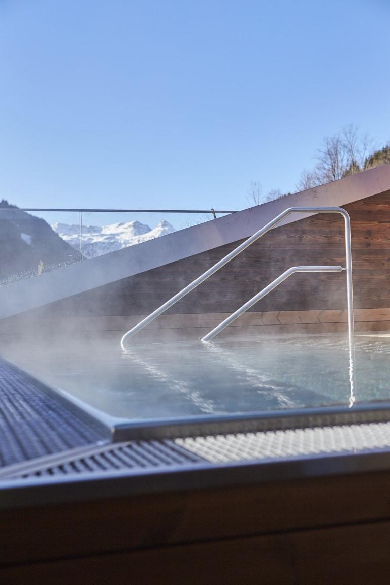 Der angenehme Außenwhirlpool mit Blick in die umliegende Bergwelt