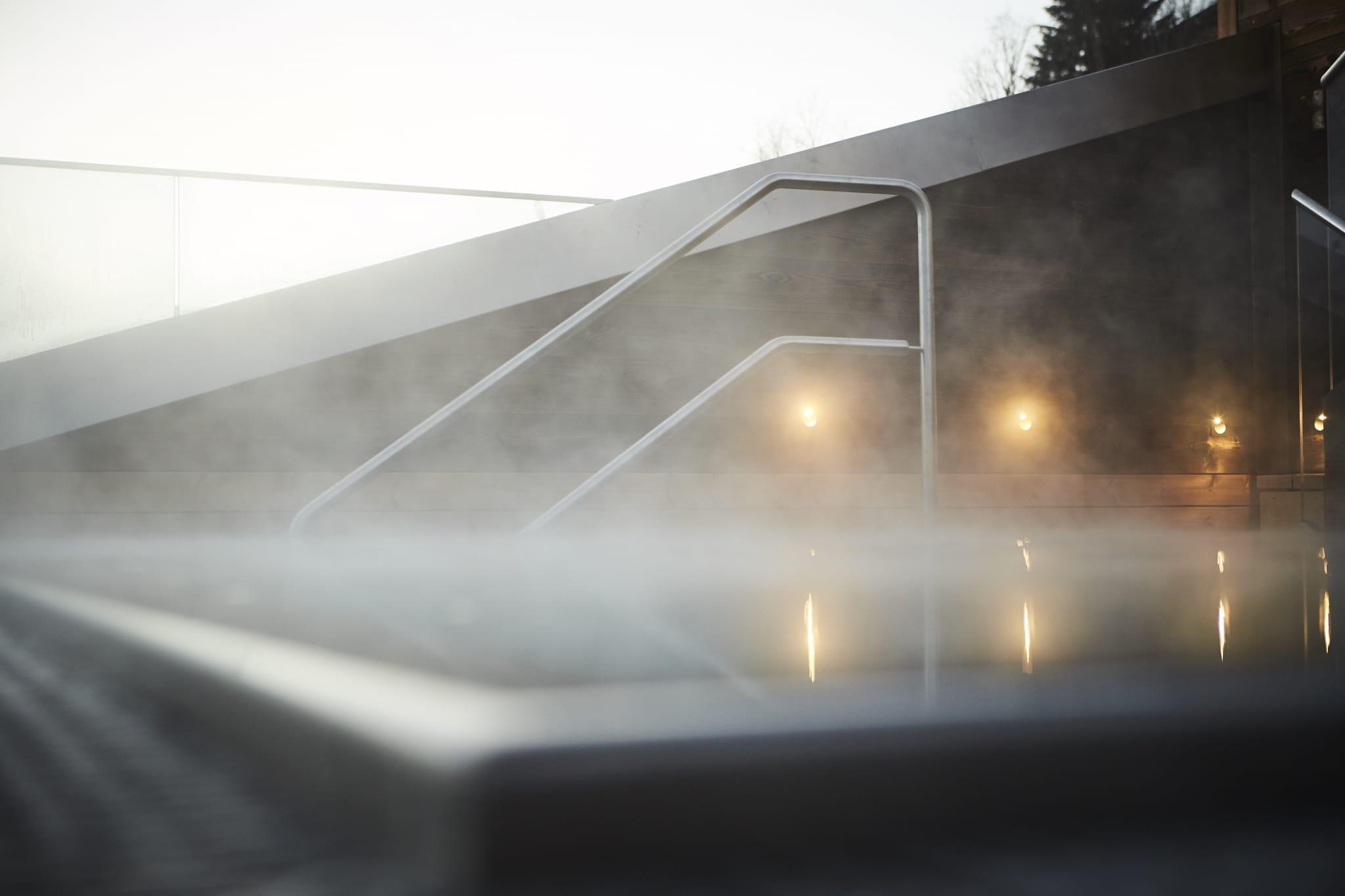Dampf steigt vom beheizten Außenwhirlpool auf