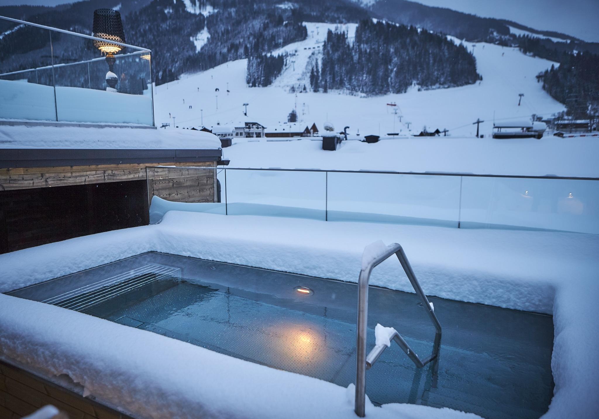Das Skigebiet Saalbach Hinterglemm im Hintergrund und der Außen-Whirlpool im Vordergrund