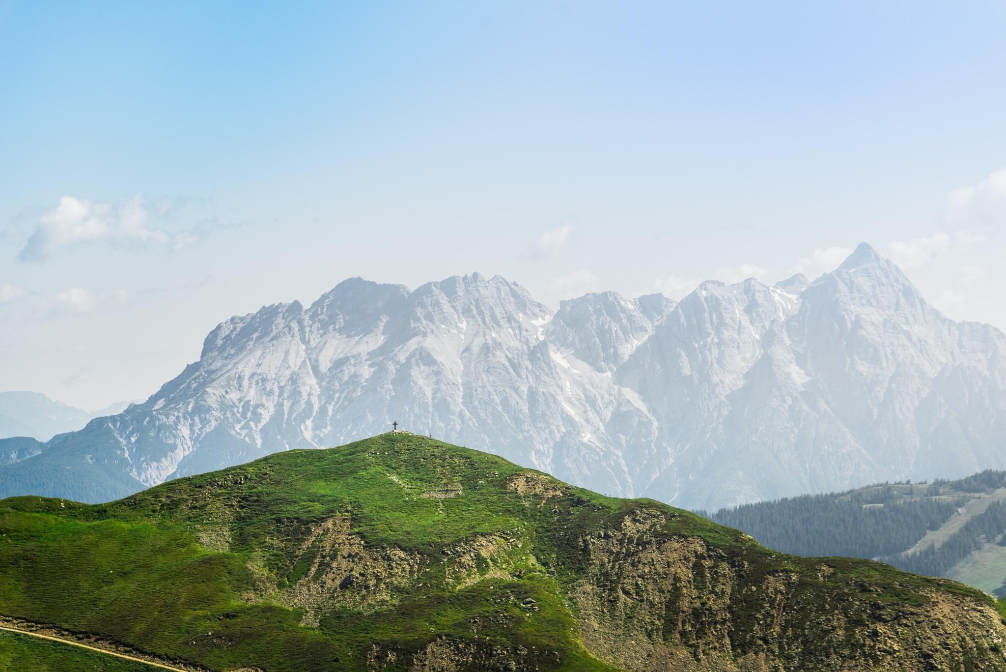 Ein grüner Berg mit Gipfelkreuz im Vordergrund und ein Bergmassiv in der Ferne.