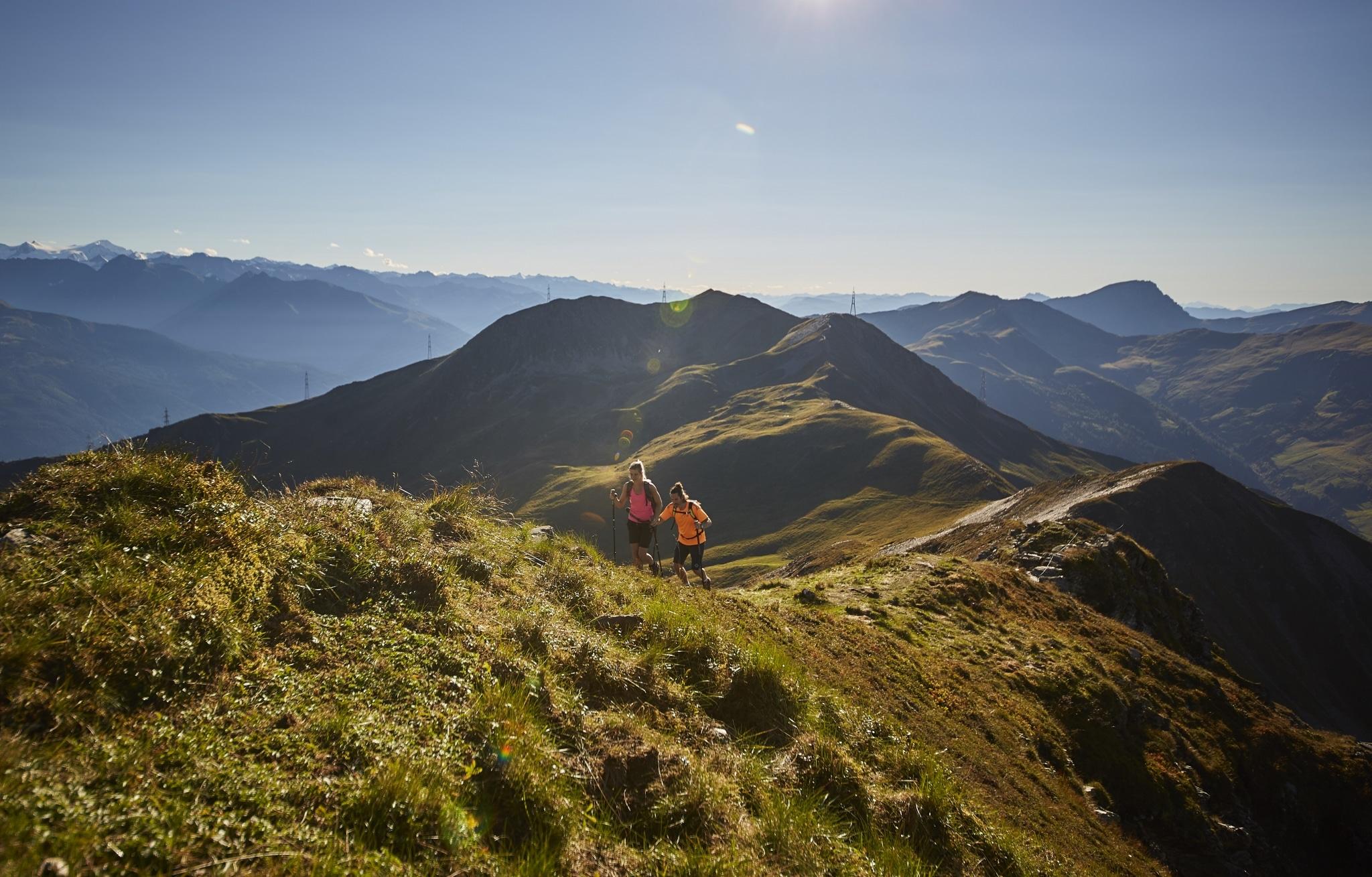 Zwei Wanderer gehen über eine Almwiesen-Kuppe bergaufwärts, im Hintergrund die Salzburger Berwelt