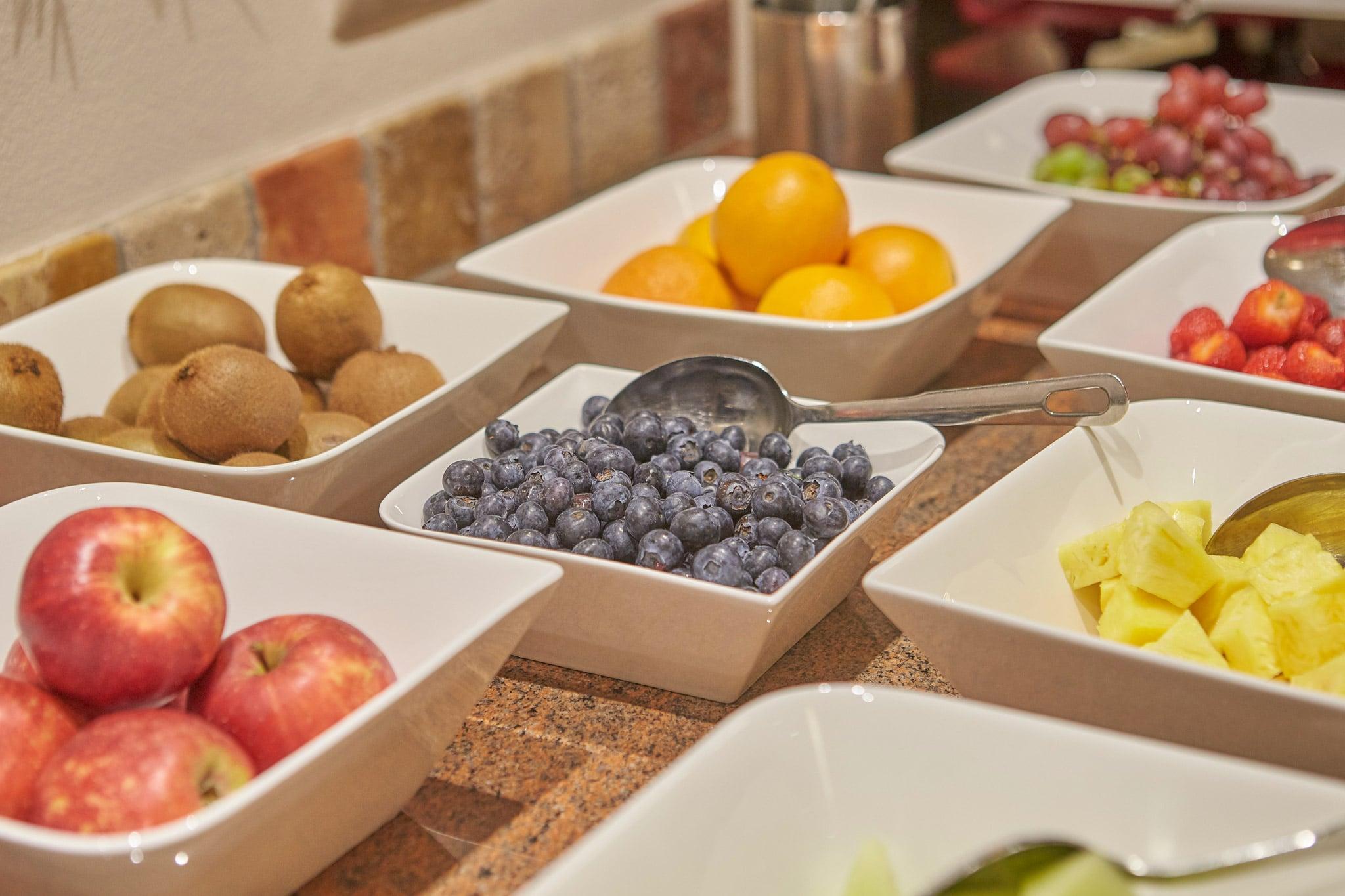 Äpfel, Kiwi, Orangen, Blaubären und weitere Früchte in weißen Schüsseln