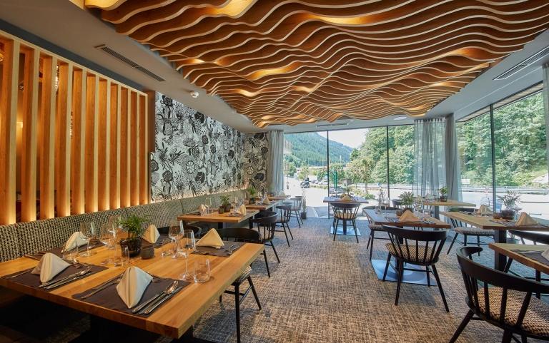 Der Speisesaal im Hotel Hasenauer mit großer Fensterfront für einen Aussicht in die Berge