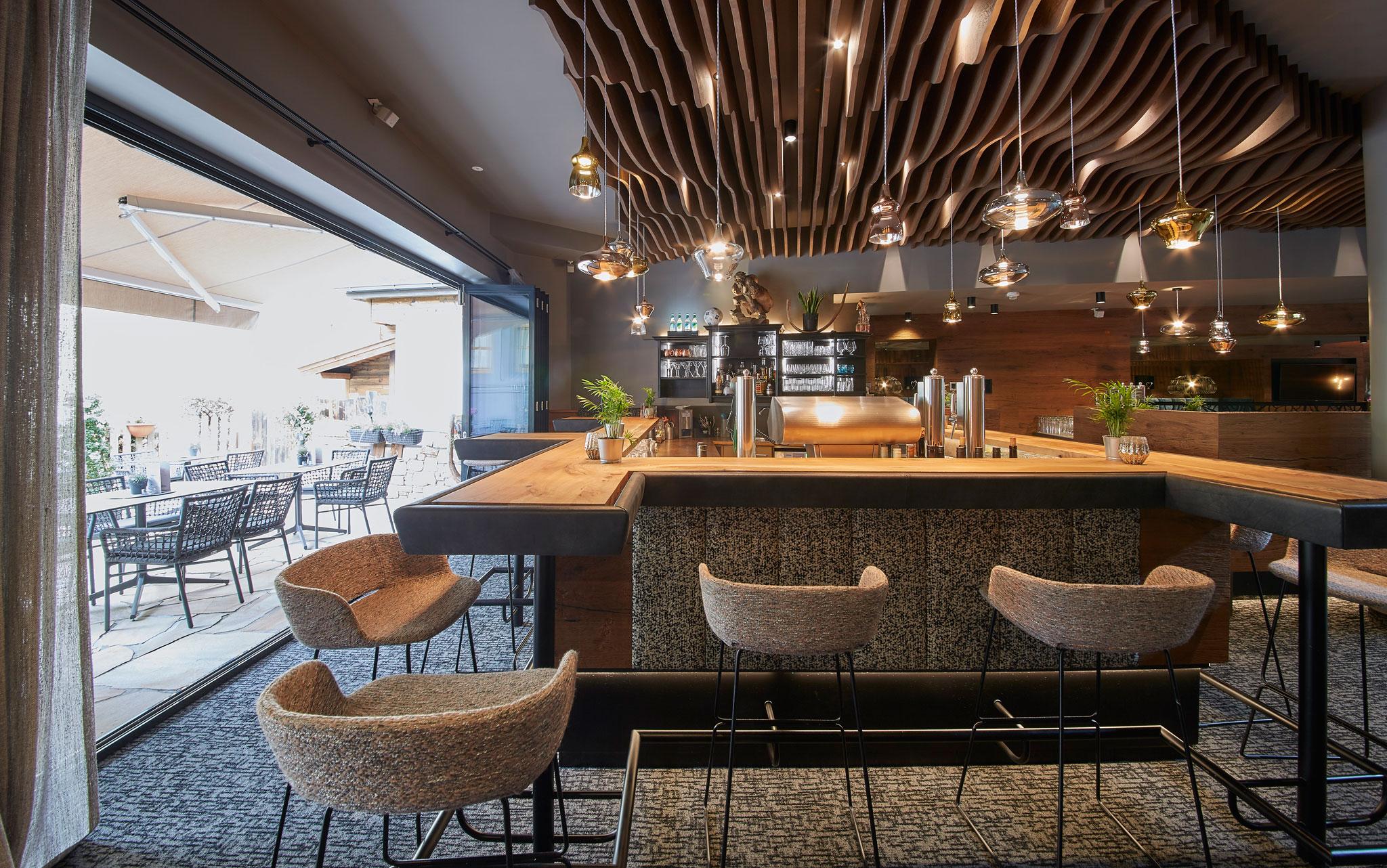 Die Bar mit stylischen Deckenlampen und Hochstühlen um die Bar herum.