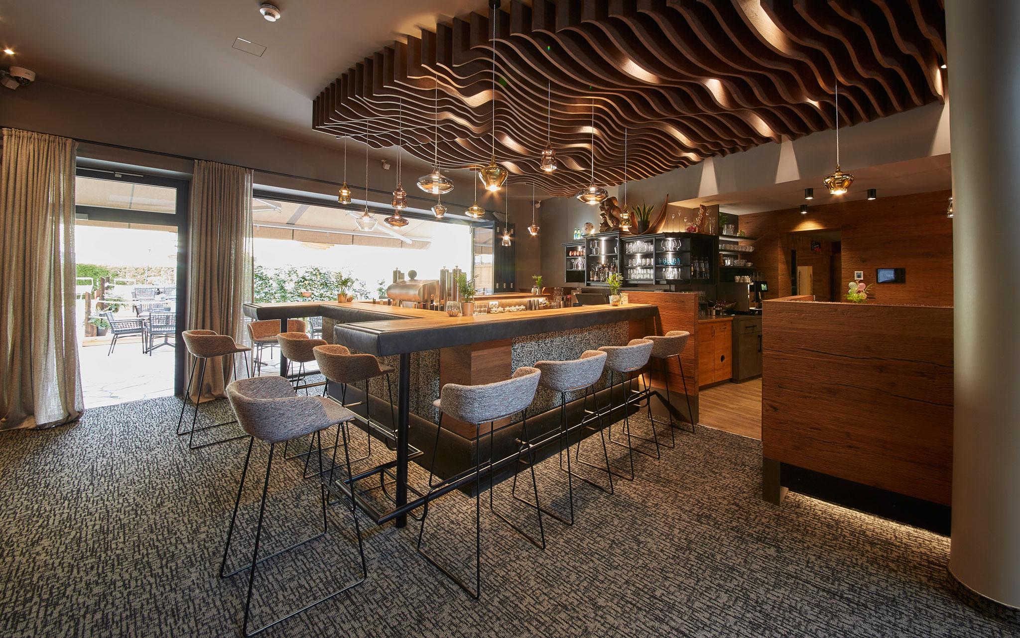Ein Blick auf die Bar mit Hochstühlen rundherum und stylischen Deckenleuchten.