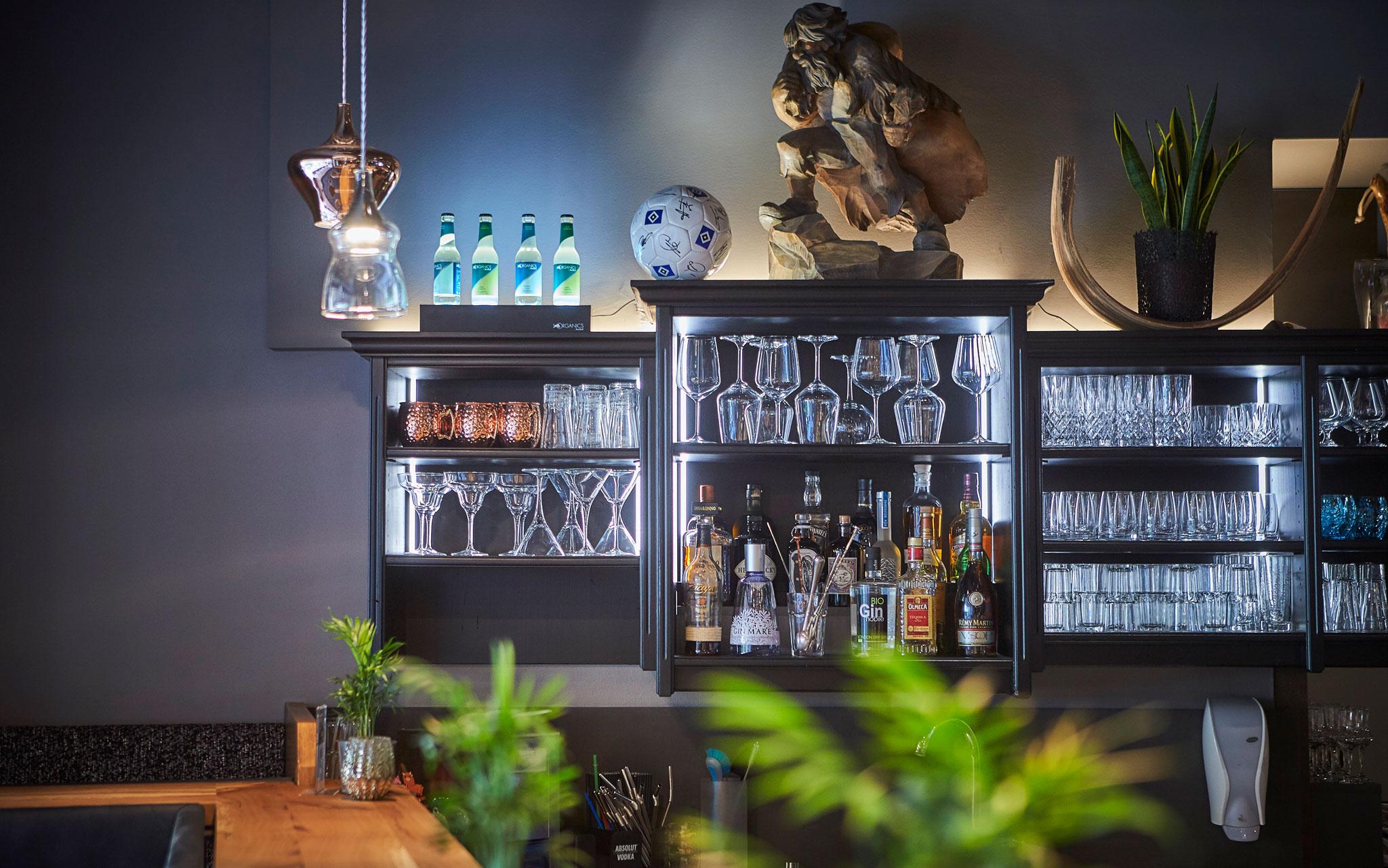 Cocktailgläser und verschiedene Flaschen stehen in der Vitrine hinter der Bar