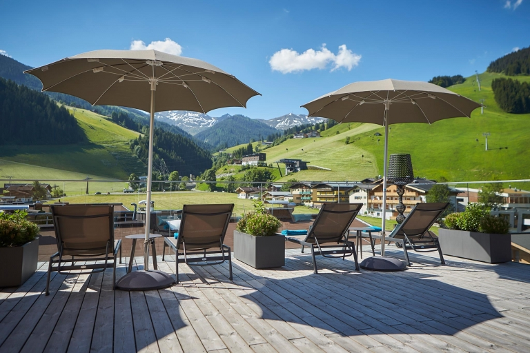 Sonnenschirme, Sonnenliegen und einen tolle Aussicht auf die umliegende Bergwelt