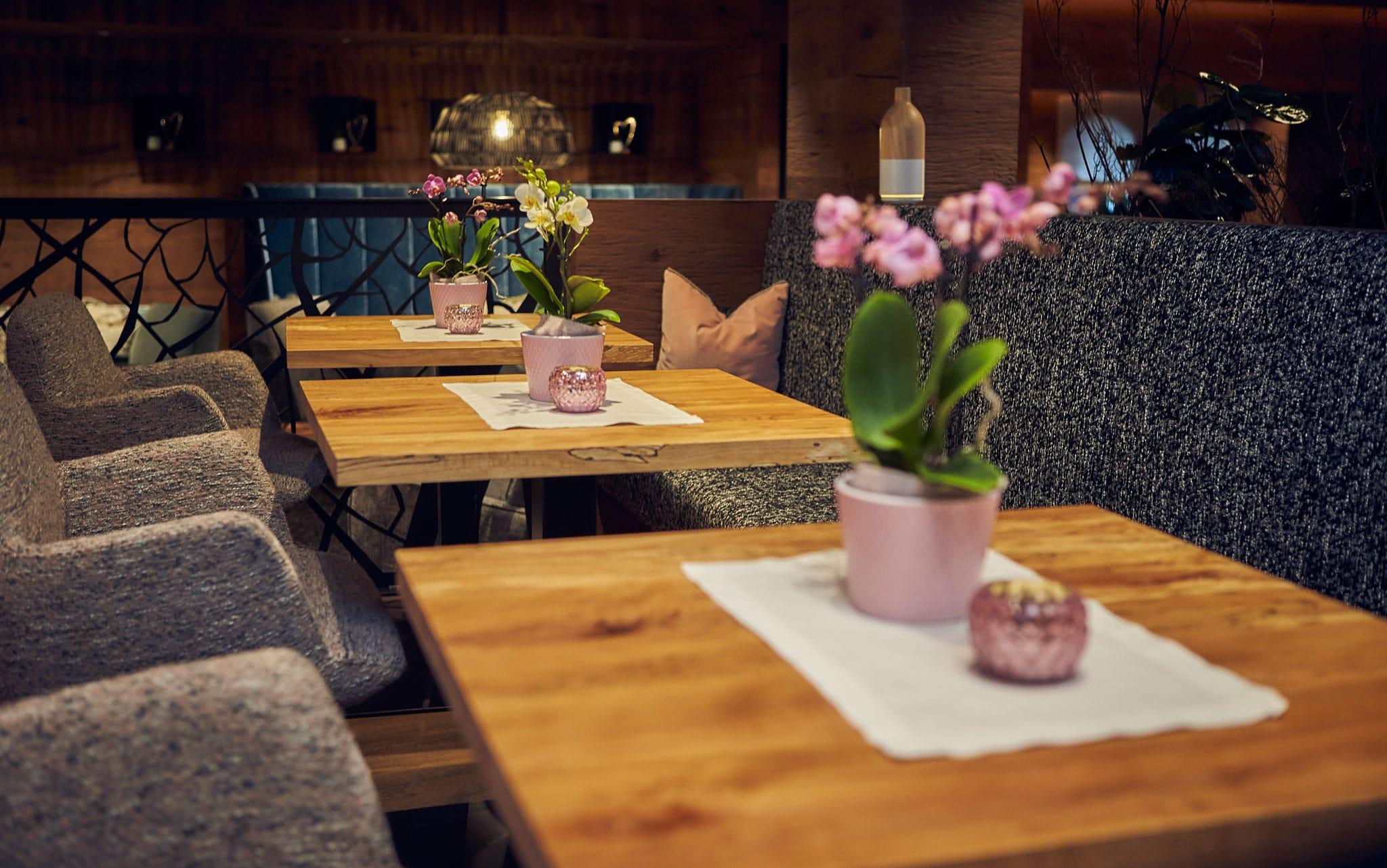 Tische in der Lounge mit jeweils einer Orchidee als Dekoration