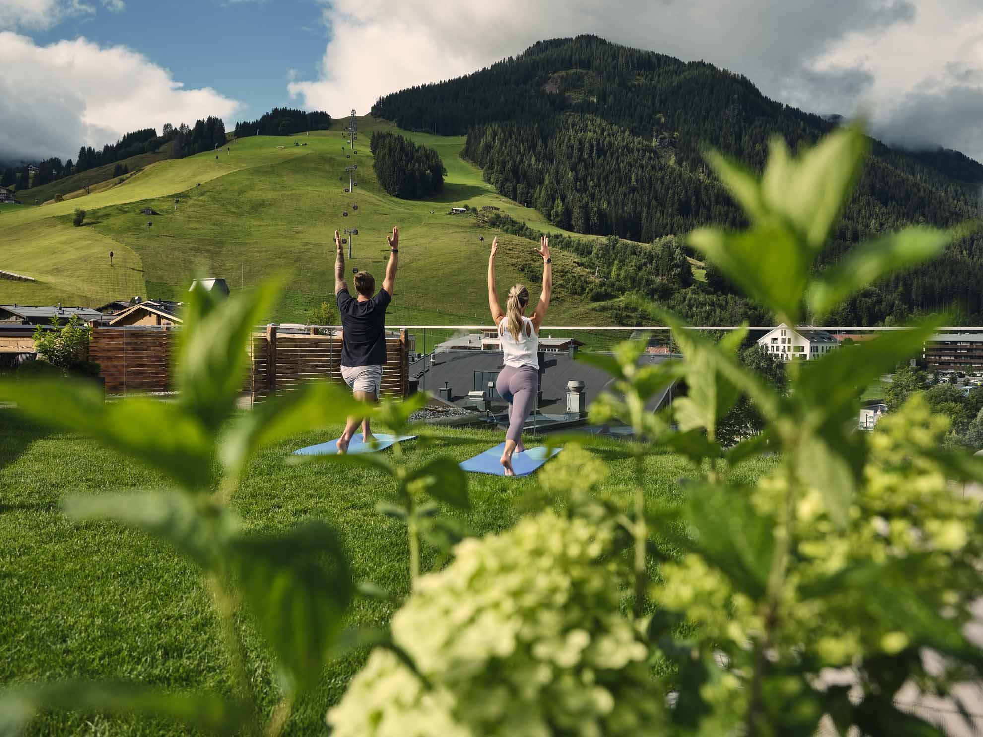 Zwei Personen machen einen Yoga-Position auf der begrünten Sonnenterrasse