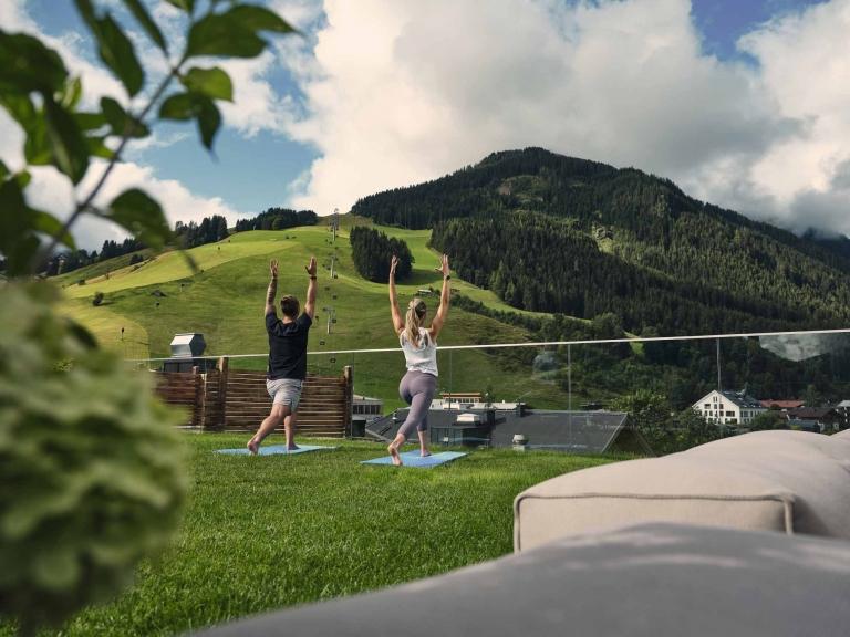 Zwei Personen machen Yoga auf der Sonnenterrasse