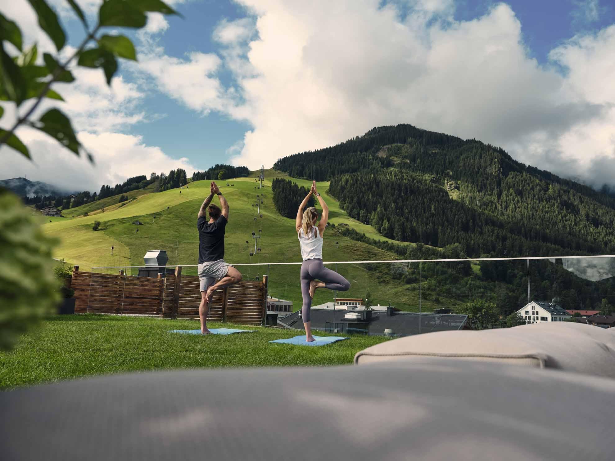 Zwei Menschen machen auf der Dachterrasse Yoga
