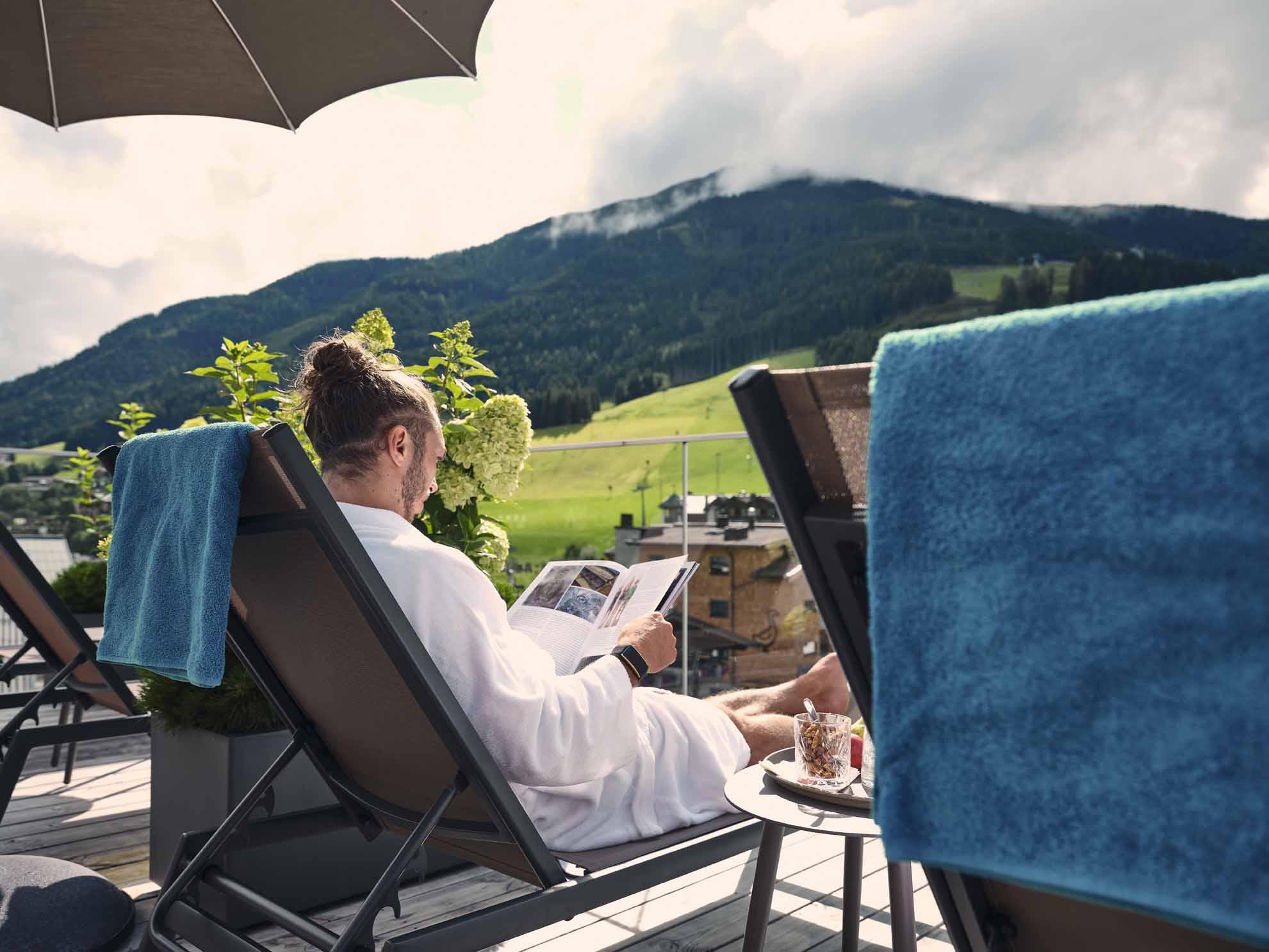 Ein Mann liest eine Zeitschrift und liegt auf dem Liegestuhl auf der Dachterrasse
