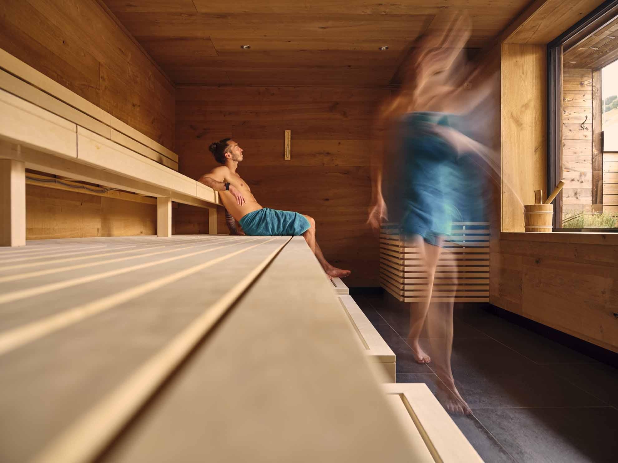 Eine Person sitzt in der Sauna und eine geht gerade hinaus