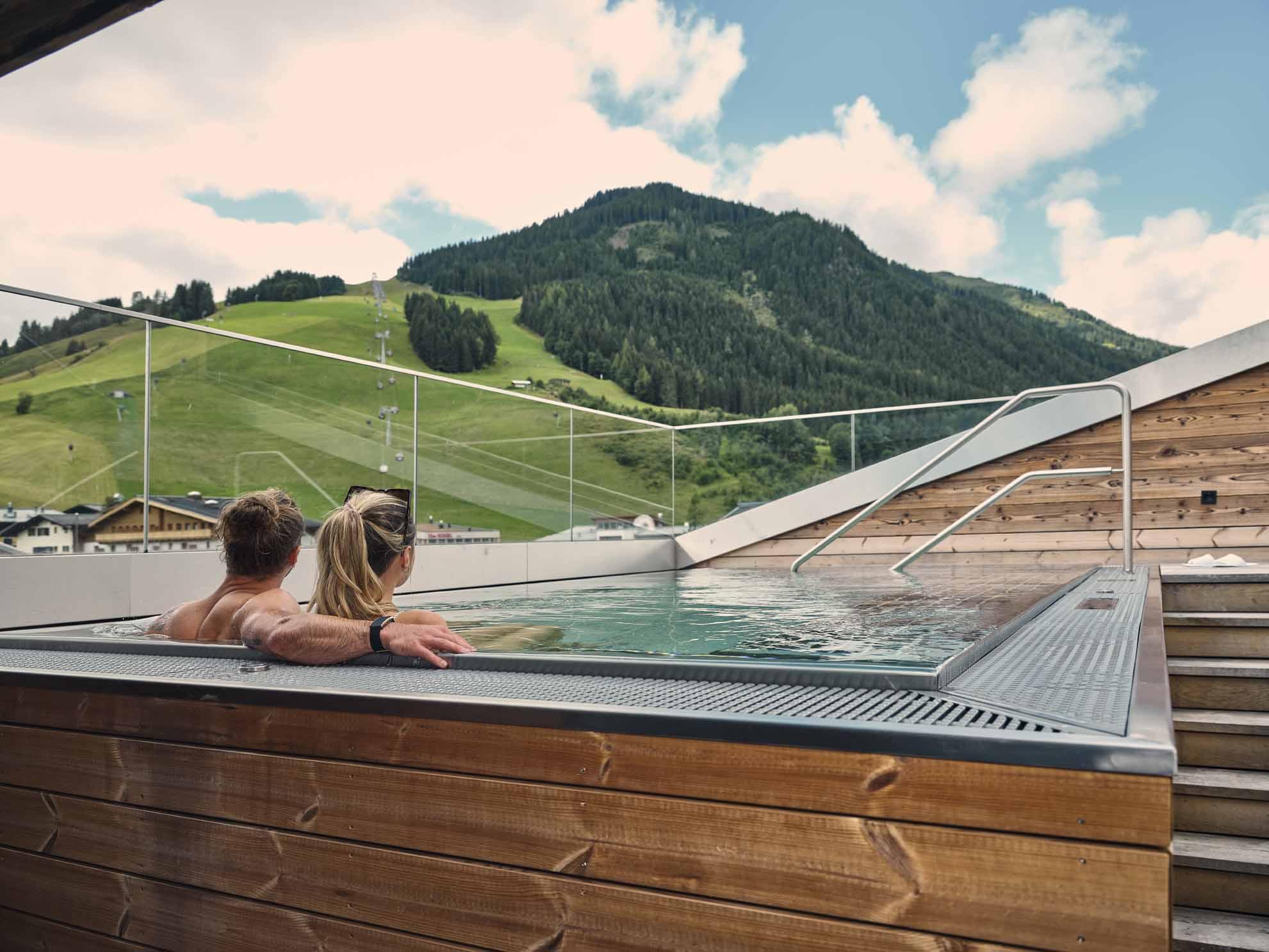 Zwei Personen im Rooftop-Whirlpool schauen in die Landschaft