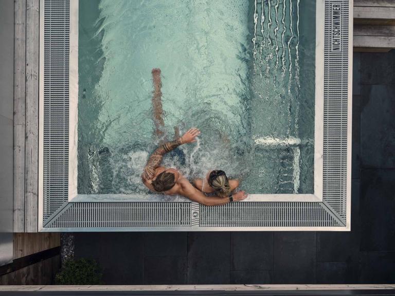Zwei Personen sitzen im Whirlpool und wurden von oben fotografiert