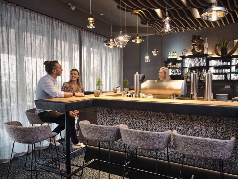 Zwei Personen sitzen an der Hotelbar und reden mit der Barfrau
