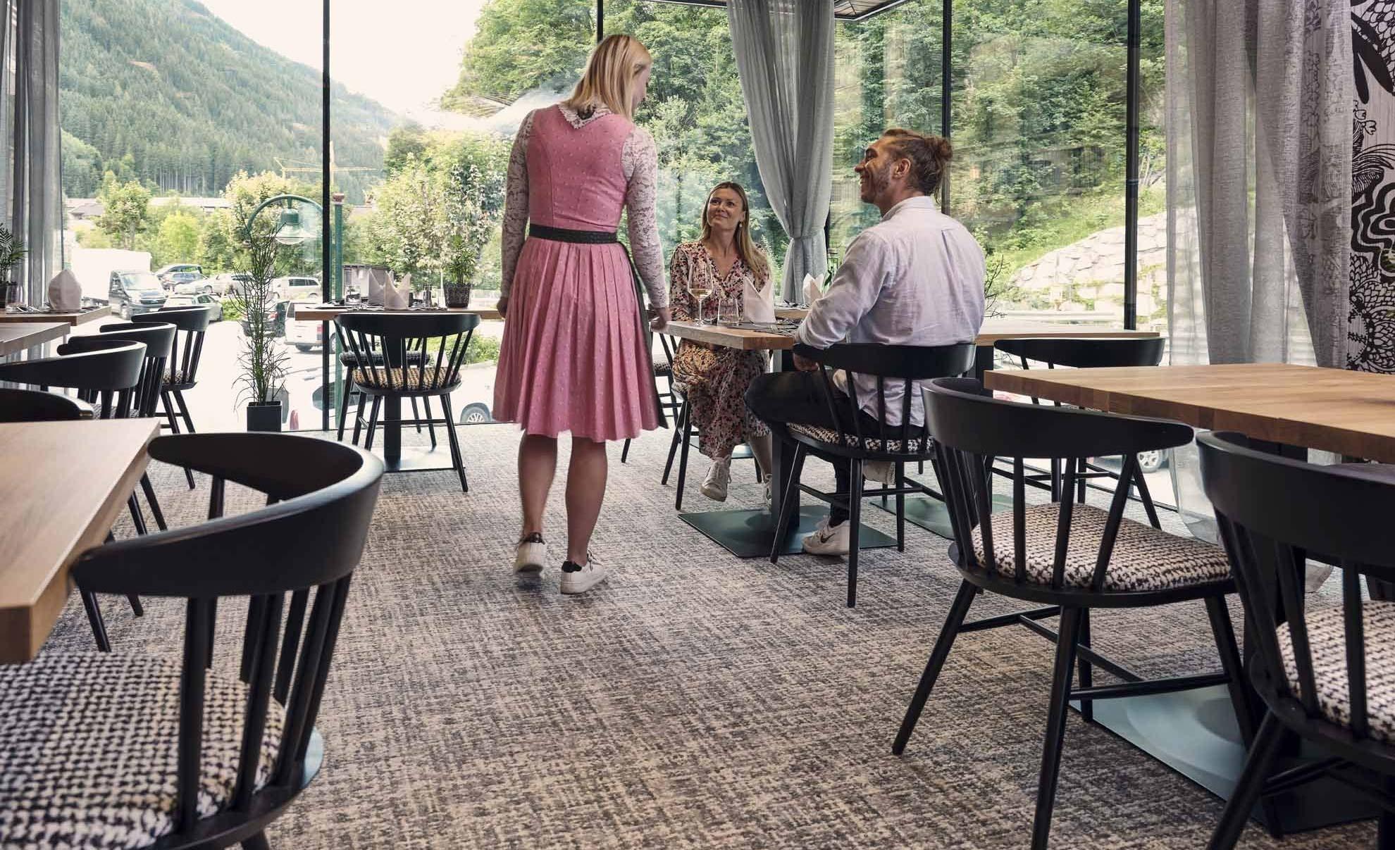 Restaurantkraft steht bei einem Tisch an welchen zwei Personen sitzen