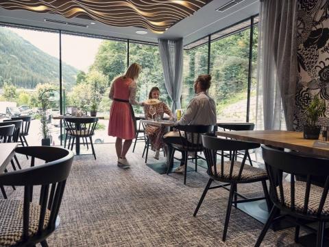 Eine Restaurantkraft serviert das Essen an einen Tisch im Restaurant