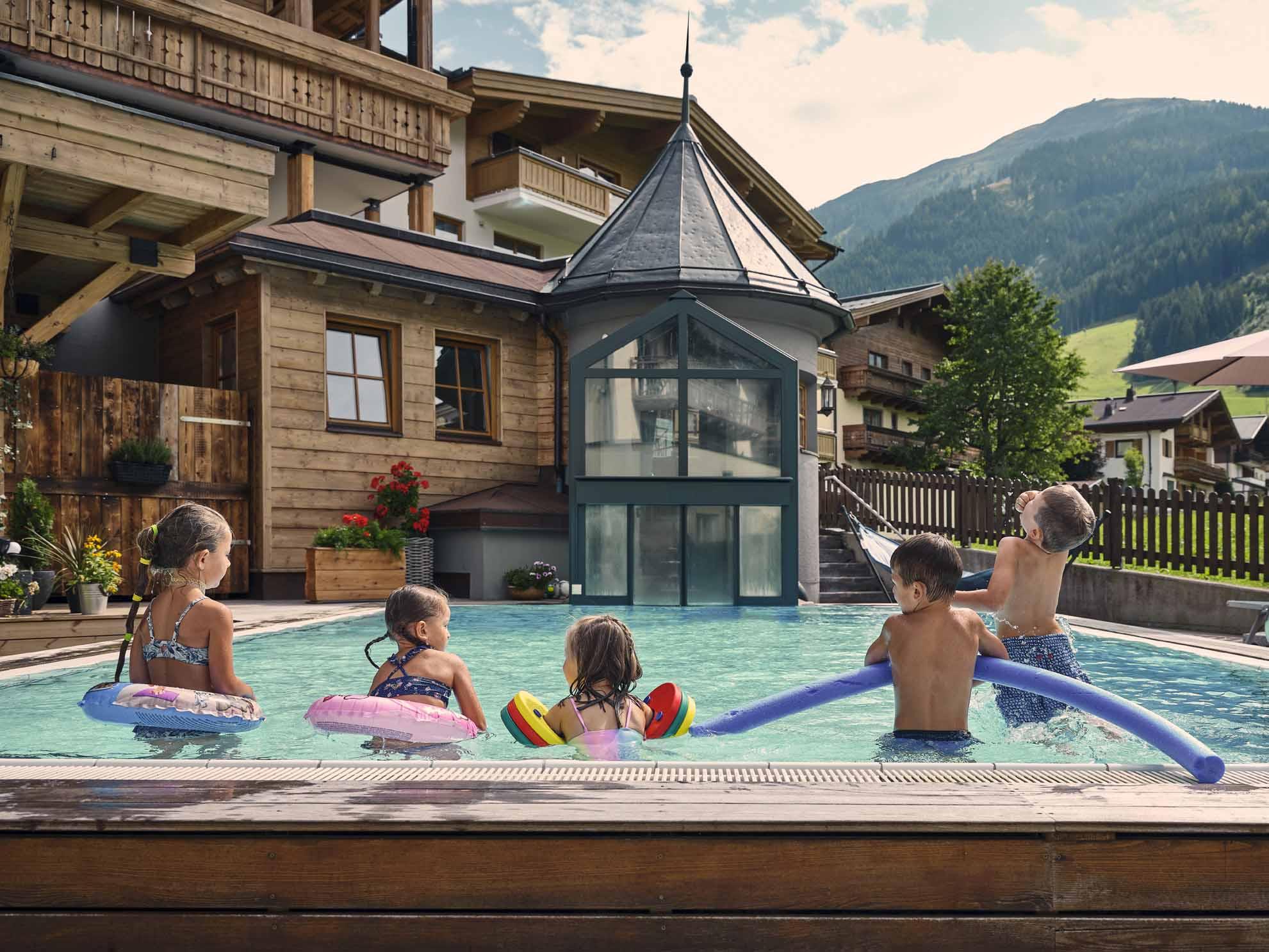 Kinder schwimmen im Außenpool
