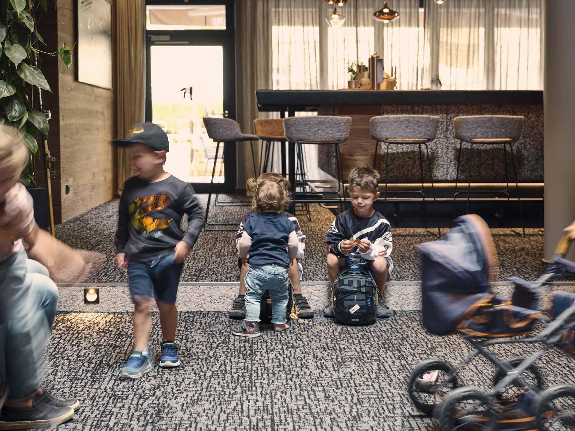 Kinder sitzen und stehen im Lobby-Bereich vom Hotel Hasenauer