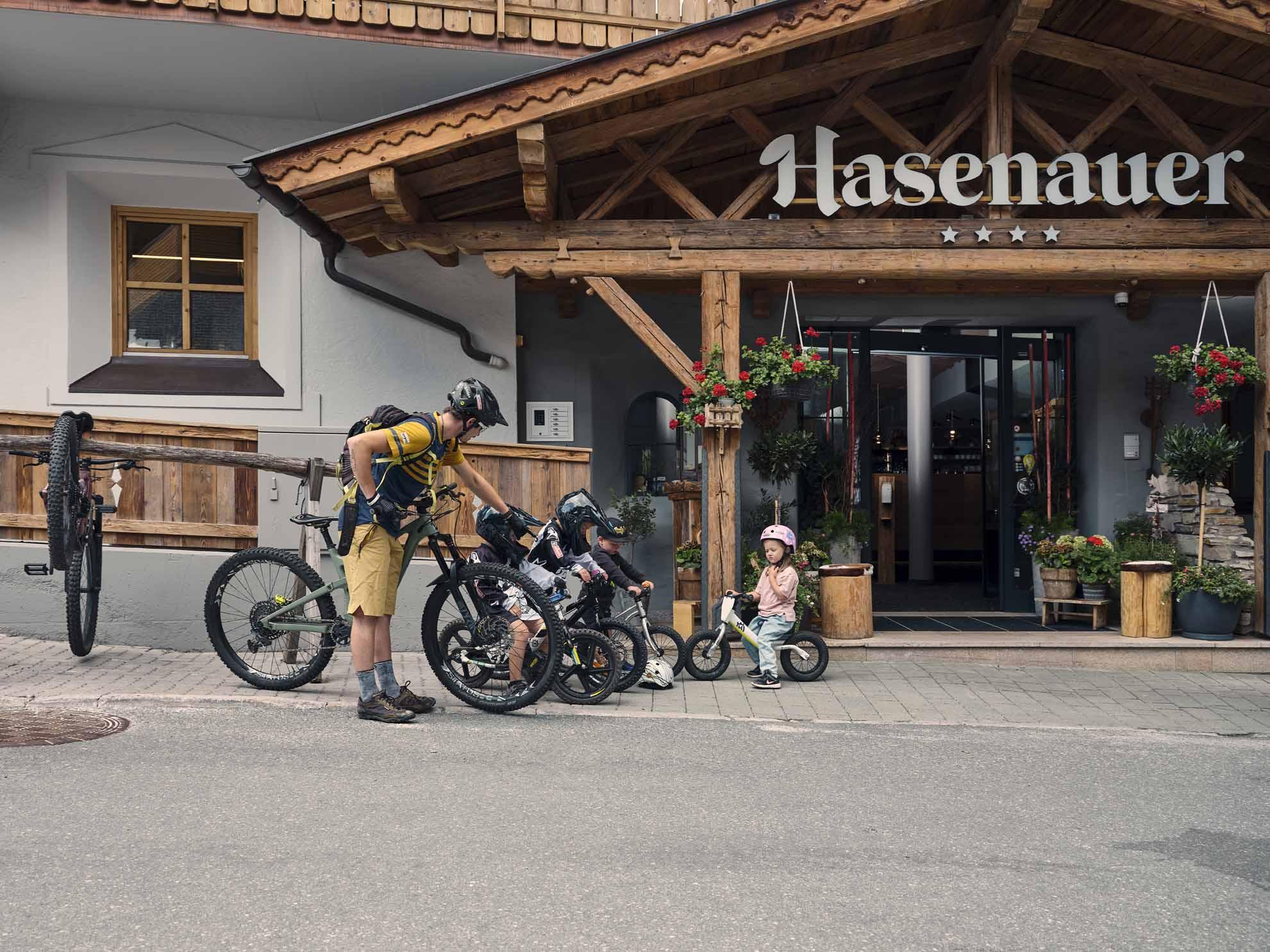 Kinder am Bike und ein erwachsener Biker stehen vor dem Hotel Hasenauer