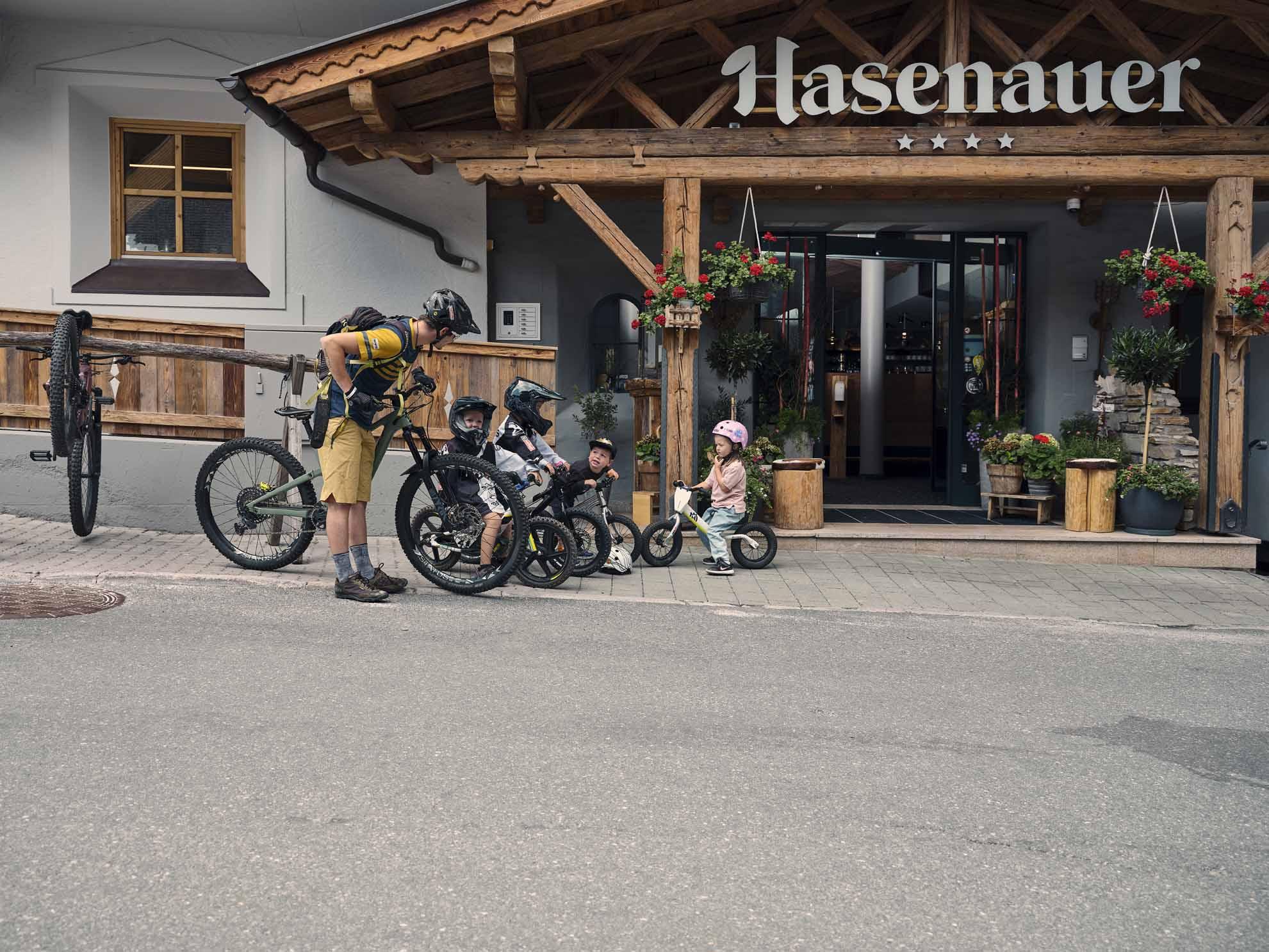 Ein Erwachsener Bike und Kinder mit Bike stehen vor dem Hotel Hasenauer