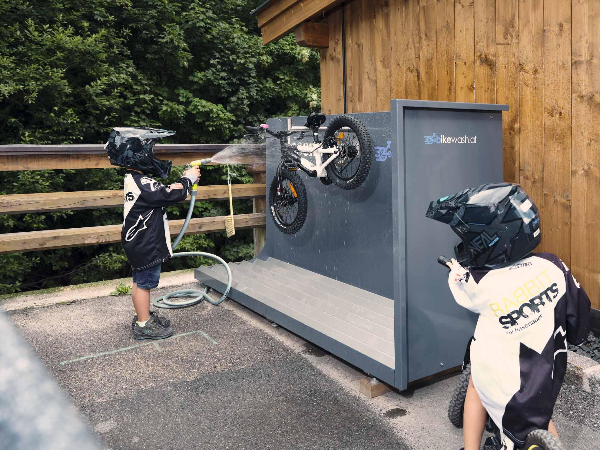 Kinder waschen das Bike am Bike-Waschplatz