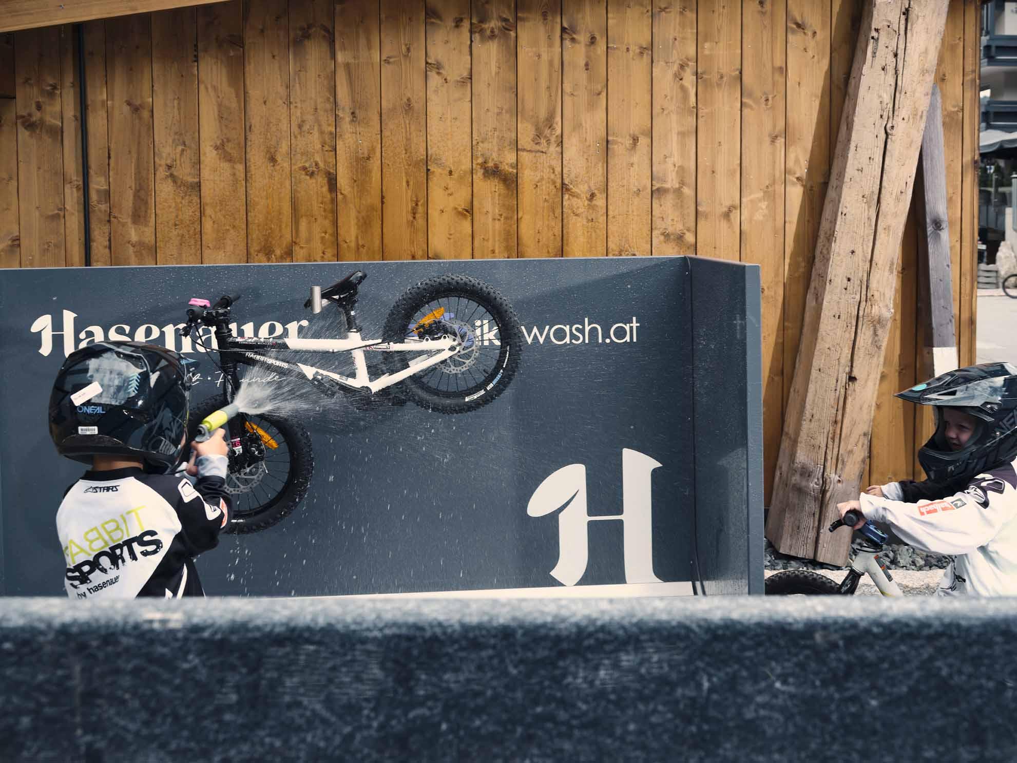 Ein Kind wäscht sein Bike beim Bike-Waschplatz