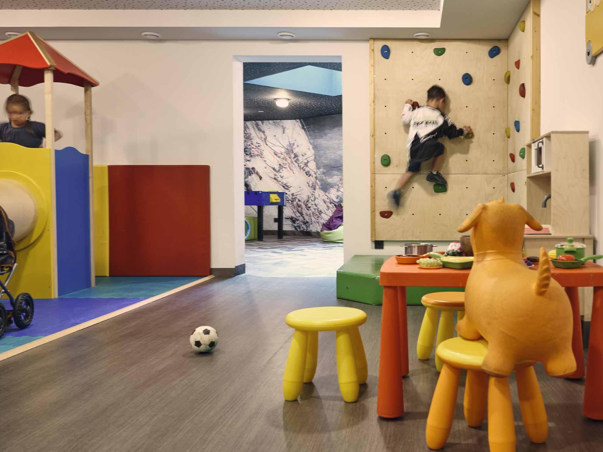 Ein Kind klettert auf die kleine Kletterwand in der Familien-Spielewelt