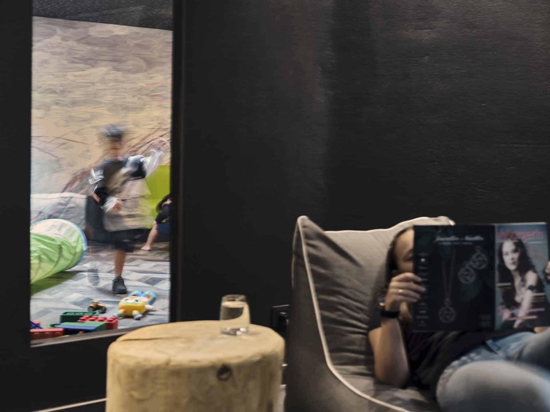 Frau liest eine Zeitschrift und im Hintergrund spielen die Kinder