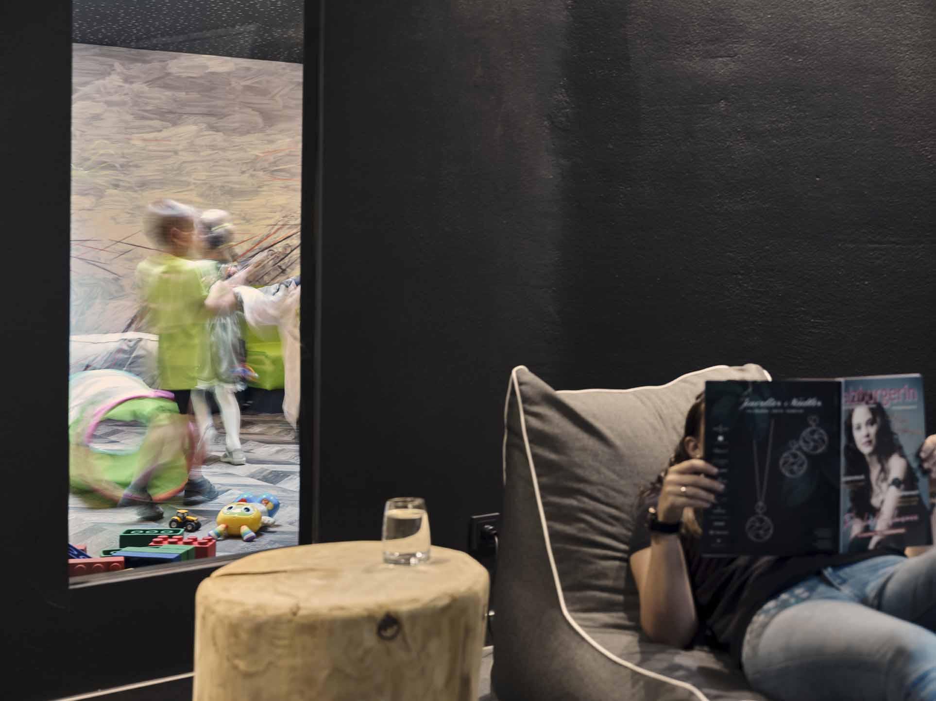 Eine Frau liegt auf dem Sitzsack und ließt, die Kinder spielen im Hintergrund