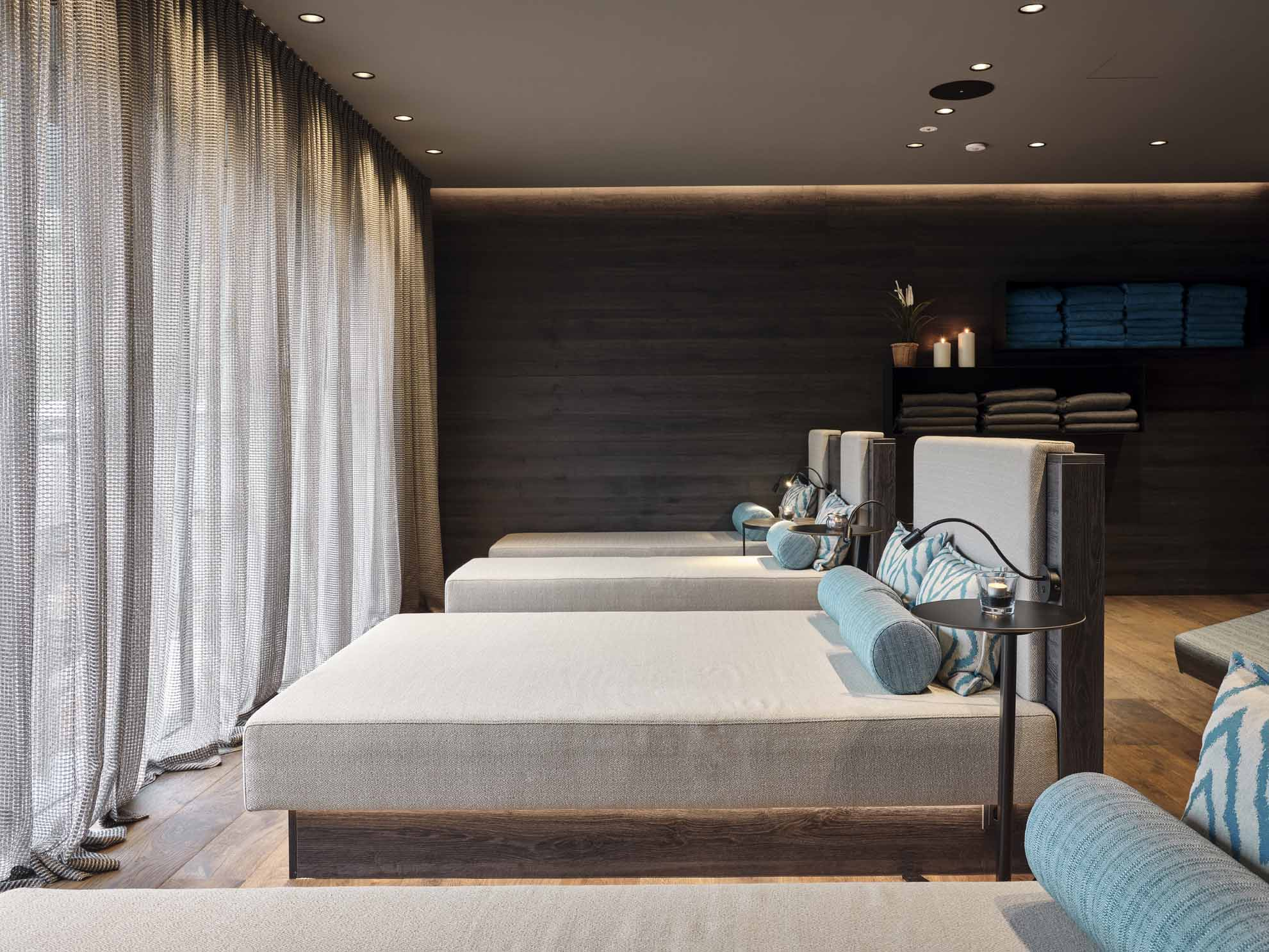 Graue Liegebetten aus Holz mit blauen Pölstern