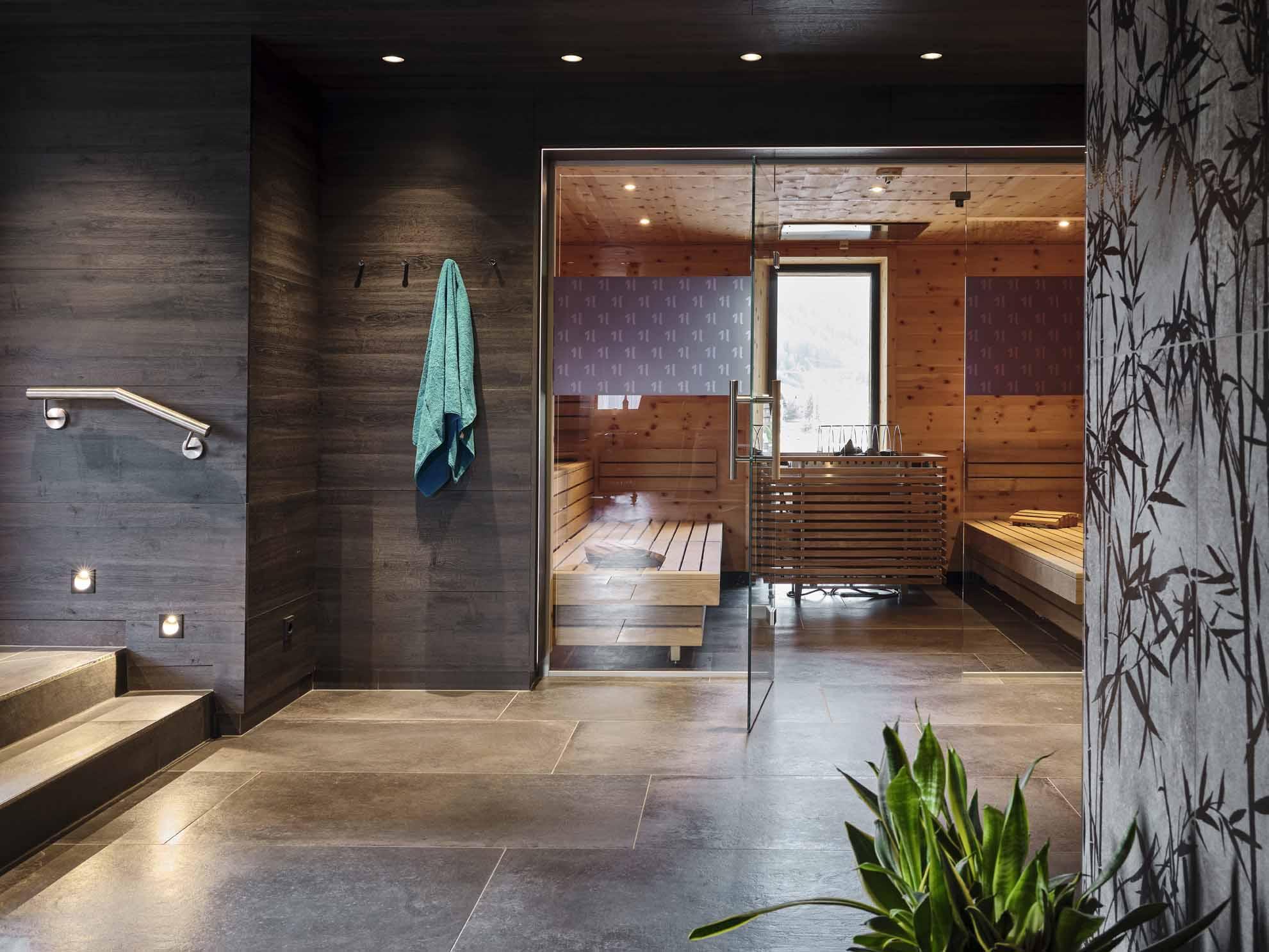 Die Sauna im Hasenauer mit offener Glastüre und einem blauen Handtuch links neben der Türe